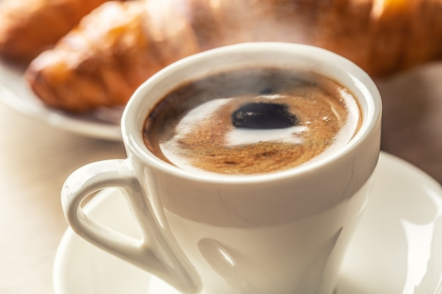 一杯のコーヒーと焼きたてのクロワッサン-イタリアまたは地中海の朝食。