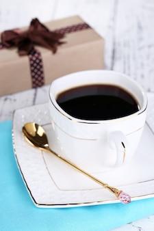 一杯のコーヒーと木製のテーブルのクローズアップの贈り物