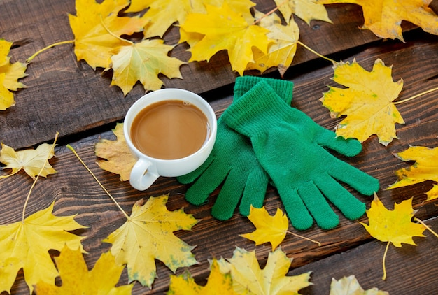 木製のテーブルのカエデの葉の横にあるコーヒーと緑の手袋のカップ。
