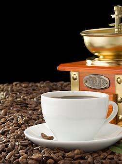黒い背景で隔離のコーヒーとグラインダーのカップ