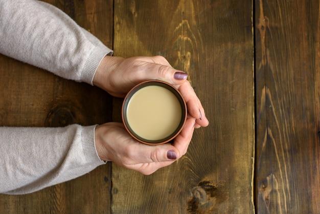 Чашка кофе и руки на деревянных фоне. вид сверху