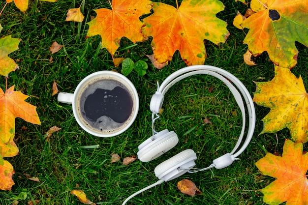 庭の緑の芝生の上にカエデの葉とコーヒーとヘッドフォンのカップ