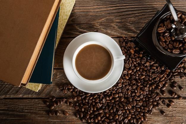 Чашка кофе и куча зерен на деревянном столе
