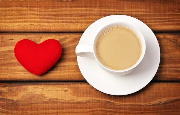 一杯のコーヒーと木製の背景にハート。