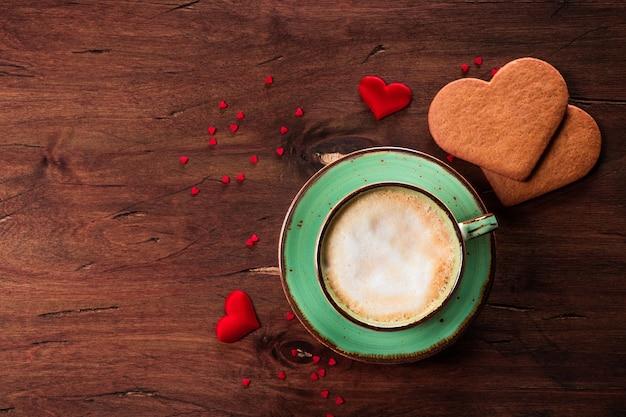 나무 배경에 커피와 심장 모양의 쿠키 컵