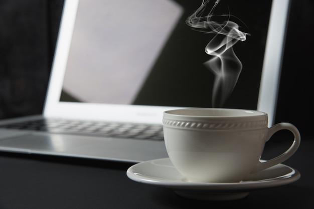 一杯のコーヒーとテーブルの上のノートパソコン