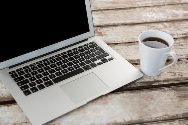 一杯のコーヒーと木製のテーブルの上のノートパソコン