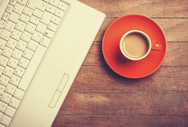 木製のテーブルの上のコーヒーとラップトップのカップ