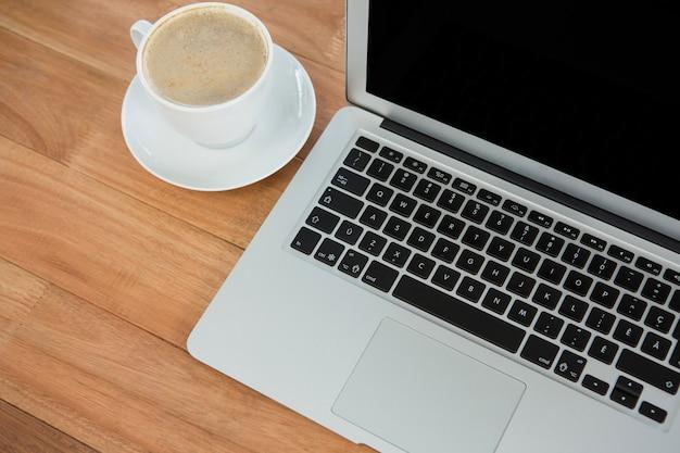 一杯のコーヒーとラップトップ