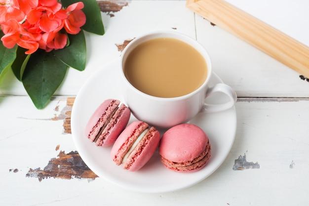 白い背景の上の皿に一杯のコーヒーとマカロンクッキー。コピースペース