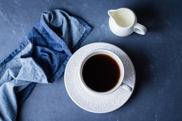 一杯のコーヒーとミルクの青い石のテーブルの背景