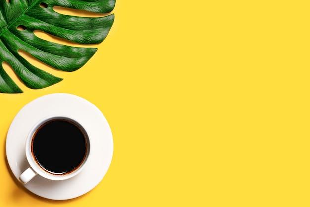 黄色の背景にコーヒーとモンステラの葉のカップ。コーヒーカップの上面図。