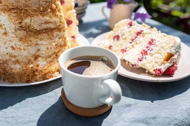 Чашка кофе и кусок домашнего малинового бисквитного торта в саду на ярком солнечном мор