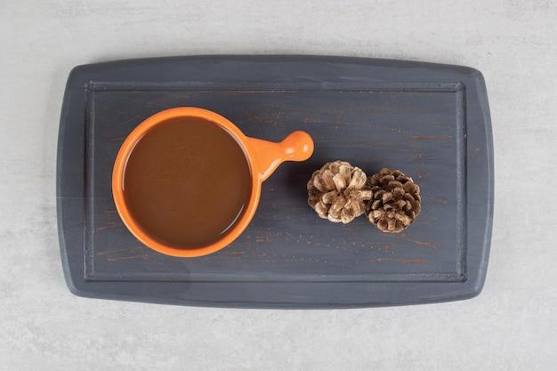 Чашка кофе и шишки на темной тарелке