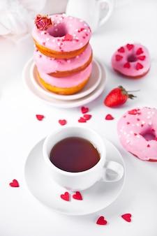 Чашка кофе и розовые пончики на белом фоне. концепция дня святого валентина.