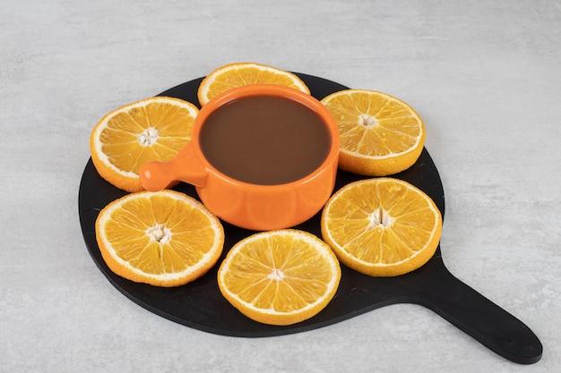 커피 한잔과 어두운 보드에 오렌지 조각 접시