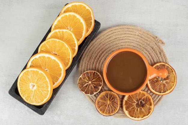 Чашка кофе и тарелка дольки апельсина