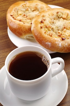 テーブルの上にリンゴとコーヒーと丸いパンのカップ