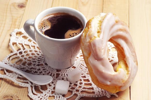 木製のテーブルの上のコーヒーと丸いケーキのカップ