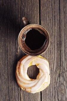 ヴィンテージの木製の背景にアイシングとコーヒーと丸いケーキのカップ。上面図