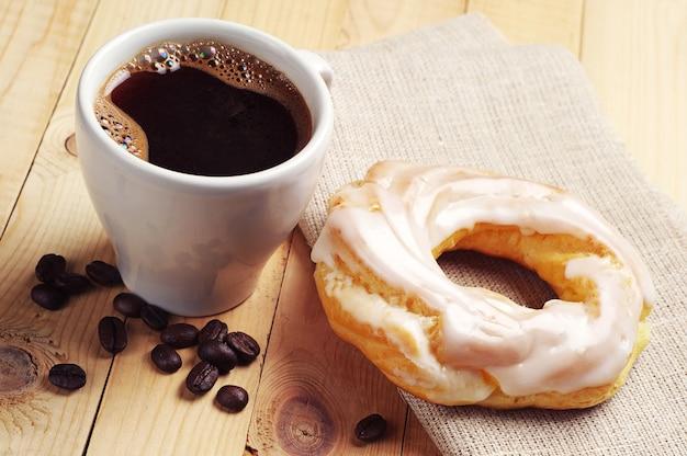 一杯のコーヒーと木製のテーブルにアイシングと丸いケーキ