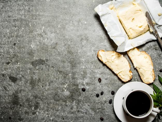 一杯のコーヒーとサンドイッチ。石のテーブルの上。