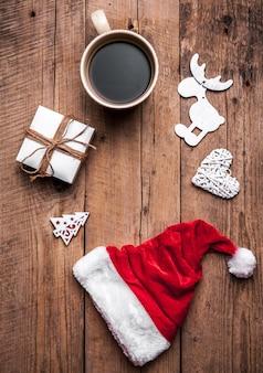 一杯のコーヒーとサンタの帽子、クリスマスセット、ギフト、クリスマスツリー。お祝い