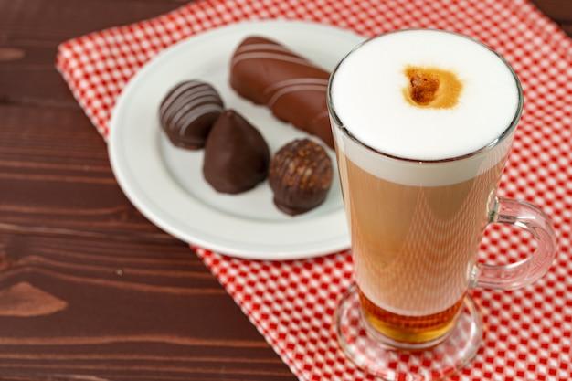 木のテーブルの上のチョコレート菓子とコーヒーとソーサーのカップをクローズアップ