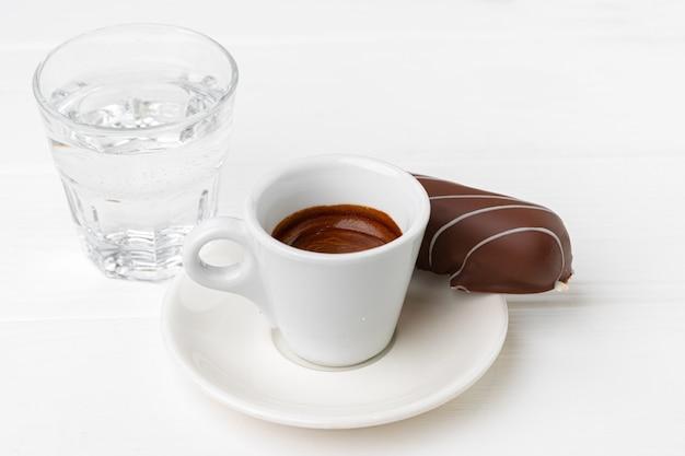 木製のテーブルにチョコレート菓子とコーヒーとソーサーのカップをクローズアップ