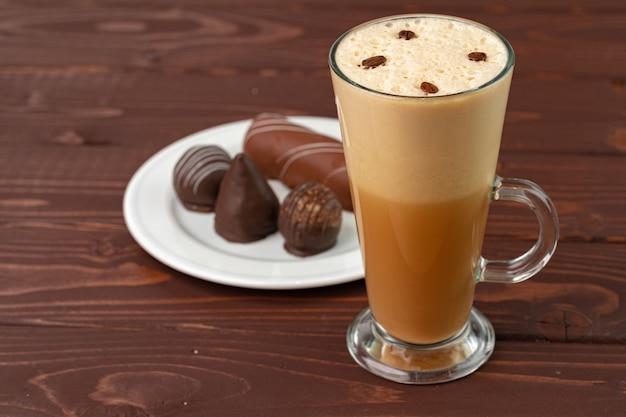 木製のテーブルにチョコレート菓子とコーヒーとソーサーのカップ