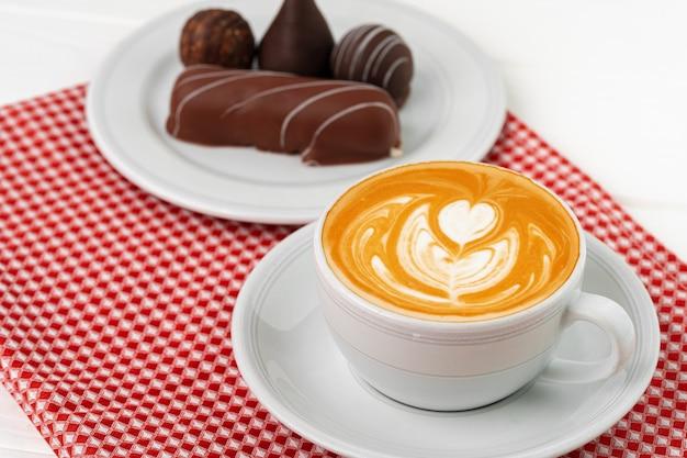 Чашка кофе и блюдце с шоколадными конфетами на деревянном столе