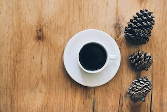Cup of coffee and saucer with three pinecones on wooden textured backdrop