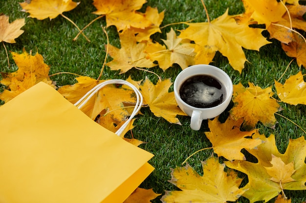 緑の草の上の黄色いカエデの葉の横にあるコーヒーとショッピングバッグのカップ