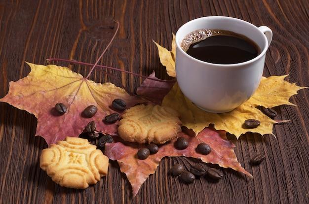 Чашка кофе и песочное печенье на деревянном столе с осенними листьями