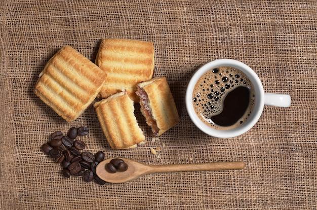 Чашка кофе и песочное печенье с джемом на столе, вид сверху