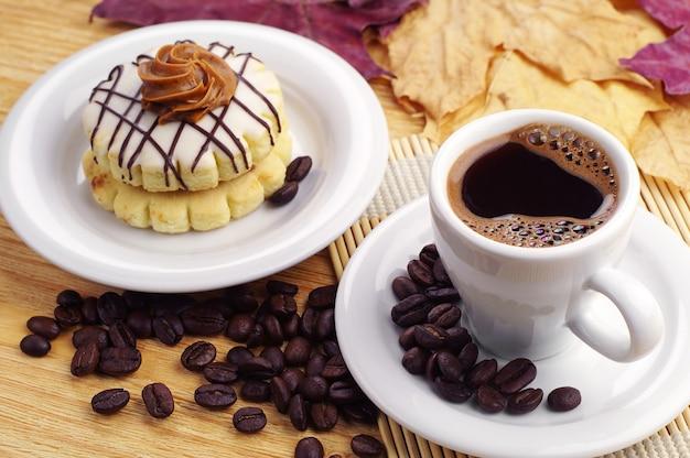 Чашка кофе и небольшой торт на столе
