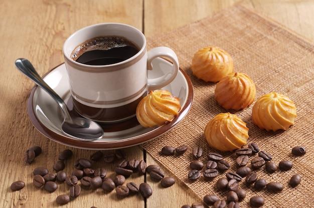 一杯のコーヒーと木製のテーブルに小さなカスタードケーキ
