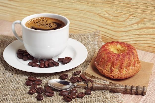 나무 테이블에서 아침 식사로 커피 한 잔과 달콤한 컵케이크