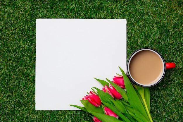 緑の芝生の上の正方形の段ボールの近くにコーヒーとチューリップのカップ
