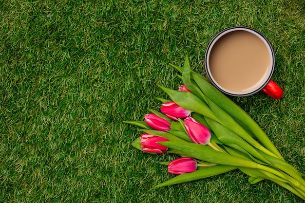 緑の草の上のコーヒーとチューリップのカップ
