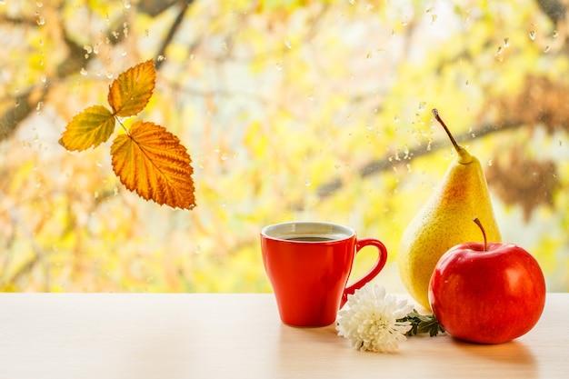 Чашка кофе, яблоко, груша, цветок и сухой лист на оконном стекле с каплями воды на размытом естественном фоне. опавшие листья и капли дождя на оконном стекле с осенними деревьями на заднем плане.