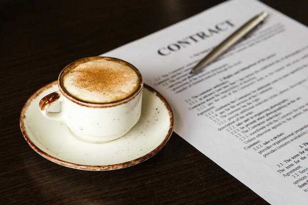 컵 커피, 볼펜, 나무 배경에 빈 계약. 비즈니스 개념.