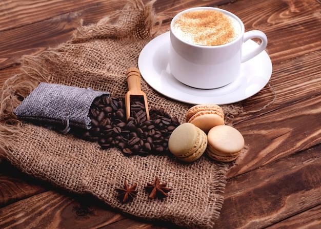 一杯のコーヒー、豆、シナモン、マカロン、木製の背景にアニス
