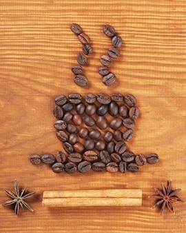 木製の背景にコーヒー豆のカップ