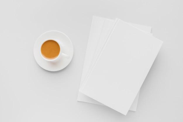本の横にあるコーヒーカップ