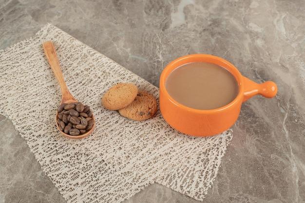 一杯のコーヒー、コーヒー豆と大理石の表面にビスケット