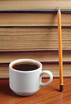 Чашка кофе, книга и карандаш на столе
