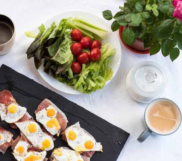 Чашка кофе. брускетта с жареным перепелиным яйцом и пармой. томатный солнечный завтрак. вид сверху