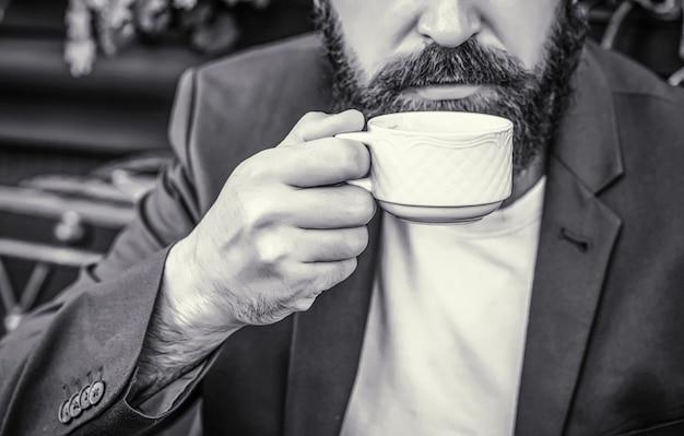 一杯のコーヒー。カプチーノと黒のエスプレッソコーヒーカップ。コーヒードリンク。あごひげを生やした男、熱いコーヒーカップを持っている手。コーヒータイム。黒と白。