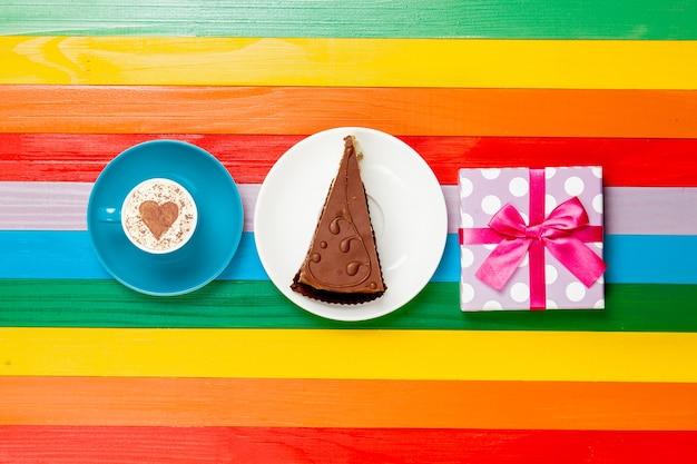 Чашка кофе капучино с тортом и подарочной коробкой на радуге